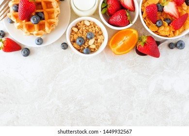 Breakfast food top border. Fruits, cereal, waffles and milk. Top view over a bright stone background with copy space.