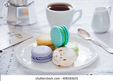 Breakfast with French colorful macarons and a coffee maker with coffee cup