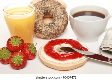 Breakfast with fresh bagels served with cream cheese, strawberry marmalade, coffee, orange juice and a newspaper