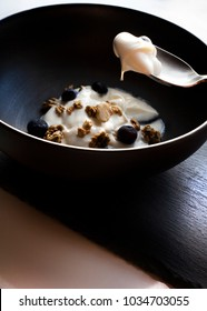 Breakfast of fresh blueberries, canola and yoghurt in blow bowl on stone slate