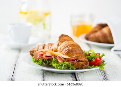 Breakfast of Fresh croissant with ham, cheese and salad leaf on white wooden background