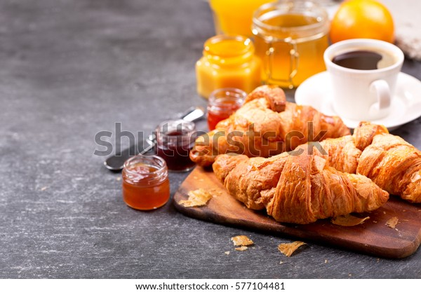 breakfast with fresh croissants and coffee on dark table