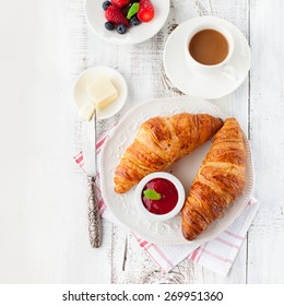 Breakfast with fresh croissants, cup of coffee and strawberry jam on a white wooden background, top view
