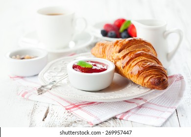 Breakfast with fresh croissants, cup of coffee and strawberry jam on a white wooden background, selective focus