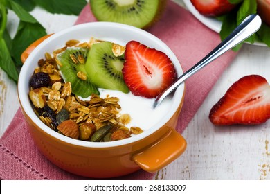 breakfast with  fresh Greek yogurt, strawberries, kiwi and granola on a white wooden table