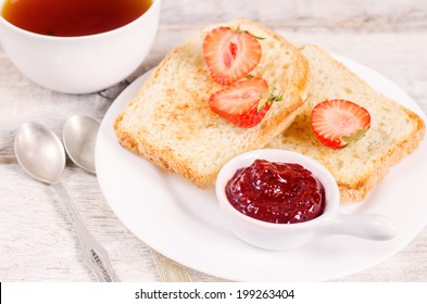 breakfast with fresh toasts, strawberries and strawberry jam on a white wood background. toning. selective focus on jam