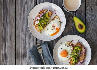 breakfast with fried egg, bruschetta with avocado and red onion and microgreens