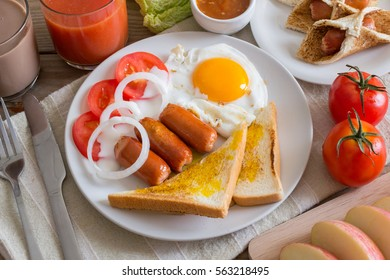 Breakfast with fried egg and tomato juice on wooden table.