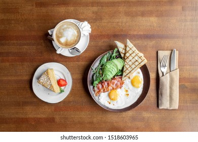 Breakfast of fried eggs with fried bacon, avocado and toast served on a wooden table with coffee and cheesecake