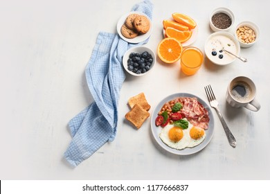 Breakfast with fried eggs, bacon, orange juice, yogurt and toasts. Top view with copy space