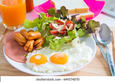 Breakfast with fried eggs, bacon, sausages, toasts and fresh salad