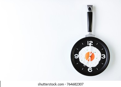 Breakfast with fried eggs on frying pan in shape of clock isolated on white background with copy space, top view. Breakfast time concept. Healthy vegetarian morning food
