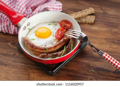 Breakfast with fried eggs, sausages and tomatoes