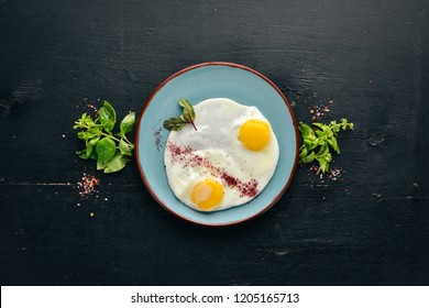 Breakfast. Fried eggs. Top view. Free space for your text. On a wooden background.