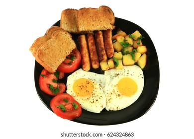 Breakfast of fried sausages, potatoes, eggs, sliced tomatoes seasoned with parsley leaves and ground black pepper and served with toast on a black dish over a white background