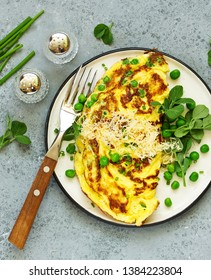 Breakfast. Frittata Italian omelet with green peas and salad.