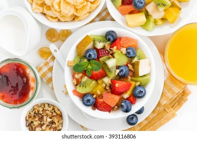 breakfast with fruit salad and corn flakes on table, top view, horizontal