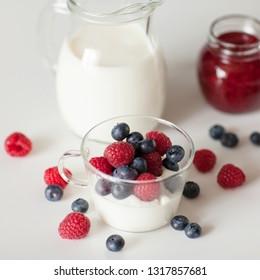 Breakfast. Glass jug with milk, yogurt, raspberry jam and raspberry and blueberry berries on white background. Dairy produce
