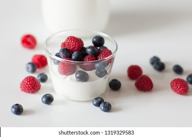 Breakfast. Glass jug with milk, yogurt, raspberry jam and raspberry and blueberry berries on white background.