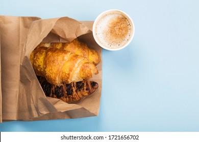 Frühstück zu gehen - Croissants und Kaffee mit Milch auf blauem Hintergrund.Lieferung von Produkten. Draufsicht, Kopienraum