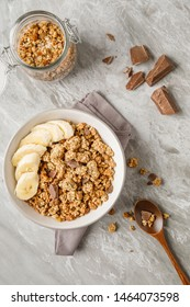 Breakfast with granola with banana. Pieces of chocolate and jar of granola on background.Stock image