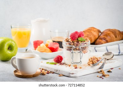 Breakfast of Granola with berries and yoghurt in a jar, with cofee and croissants