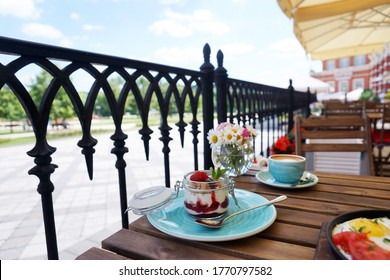 Breakfast with granola on the veranda of the summer restaurant
