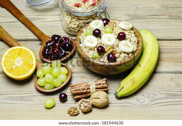 Breakfast with granola in wooden bowl,fresh fruits,cinnamon, nuts on wooden background.Top view.