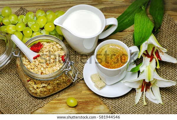 Breakfast with granola,warm milk,fresh bunch of grapes and a cup of espresso placed with beautiful lilies flower on wooden background.