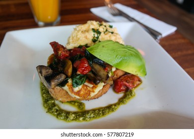 Breakfast with grilled halloumi, mushroom, bread, avocado scrambled eggs topping with nice green sauce.