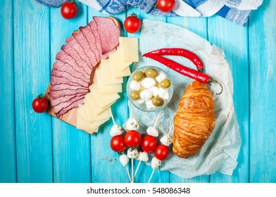Breakfast with ham,cheese, Mozzarella, cherry tomatoes and croissant on blue wood