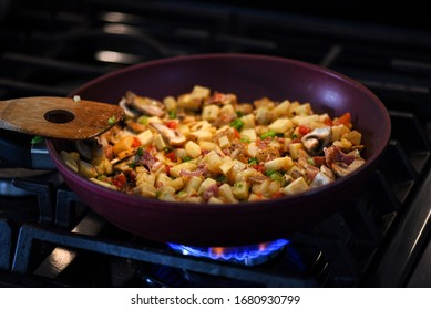 Breakfast hash mix in frying pan with wooden spatula on stove with burning flame
