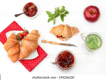 Breakfast with herbal tea, croissants and jam on the white wooden table, top view