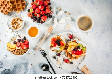 Breakfast. Home-made fresh Belgian soft wafers with honey, fresh fruits, nuts and berries; Yoghurt with granola and fruit, a cup of coffee. Light concrete table. Copy space   top view