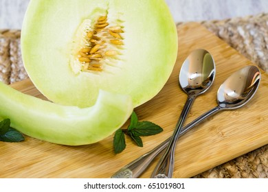 Breakfast honeydew melon on wooden cutting board with spoons and peppermint sprigs