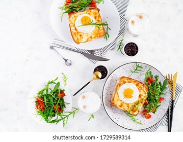 Breakfast.  Hot sandwich. Croque madame sandwich and a cup of latte macchiato coffee on the table. French cuisine.  Top view, overhead, copy space