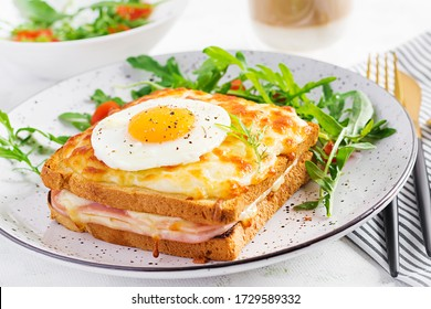 Breakfast.  Hot sandwich. Croque madame sandwich and a cup of latte macchiato coffee on the table. French cuisine. Copy space