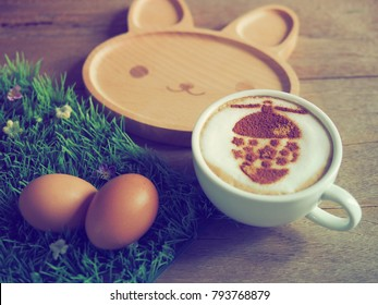 Breakfast idea with soft-boiled eggs and coffee cup with easter egg on frothy surface, wooden background with bunny shaped plate. (close up, selective focus, vintage filter)