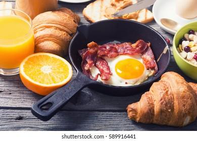 Breakfast including fried egg , croissant, orange juice , muesli and bread
