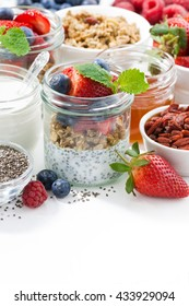 Breakfast in a jar, chia with berries and oat flakes and ingredients, vertical, closeup