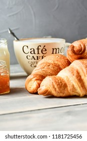 Breakfast is a large beige Cup of coffee with milk and croissants and apple jam on a wooden table. on the Cup inscription in French (top down: mocha coffee, coffee with milk, coffee without sugar)