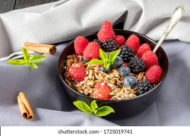 Breakfast meal with cereals berries and mint in a black bowl on gray tablecloth.