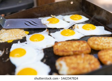 Breakfast meal of eggs and hasbrowns cooked on a flat grill