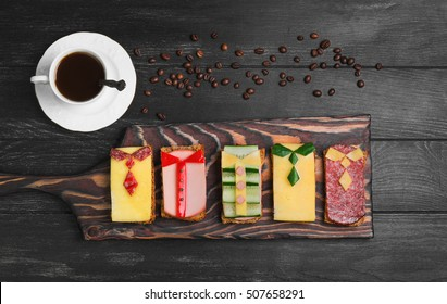 Breakfast for men. Figured sandwiches, coffee. Sausage sandwiches, cheese, vegetables. Concept sandwiches Breakfast for the day men, father's day, business lunch. Dark black wood background. Top view.