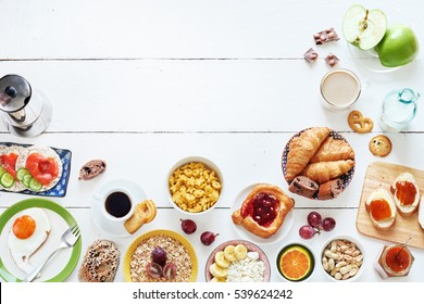 Breakfast menu food frame with a copy space. Eggs, croissants, oatmeal with banana, cereal, danish pastry, crisps with salmon, apricot jam, fresh bread, chocolate, coffee and milk on a white table.
