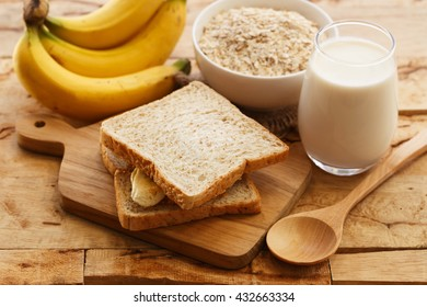 Breakfast milk, banana and bread on a wooden table.