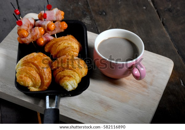 breakfast , Mini croissants, coffee, sausage, bacon wrapped skewers in a pan