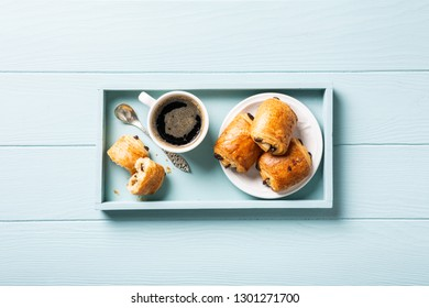 Breakfast with mini fresh croissants bun with chocolate and coffee cup on blue turquoise background. Top view. Copy space.