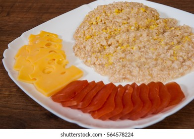 breakfast. a mix of corn and oat flakes, smoked meat and cheese on a wooden table