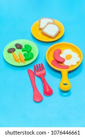 Breakfast model with egg sausage bread and salad on plastic blue table background, play dought at home, child care cooking food model, educational toys for kid creative for toddlers concept.